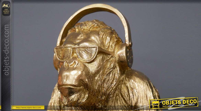 Représentation d'un gorille en résine, avec casque audio sur les oreilles, finition doré brillant, 35cm de haut