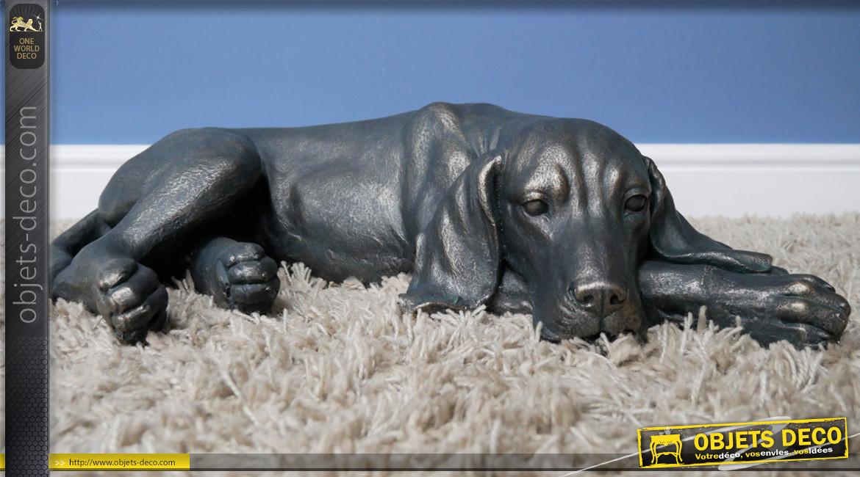 Représentation d'un chien allongé en résine finition noir charbon et reflets bronze, ambiance campagne, 58cm
