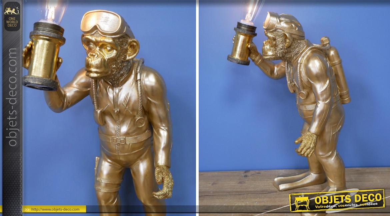 Lampe de table d'appoint en résine et verre,  représentation d'un singe explorateur, finition dorée effet brossé, 57cm