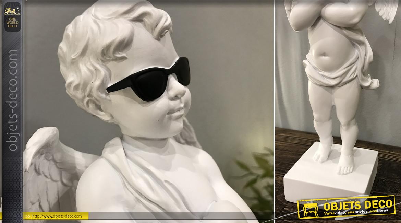Statuette d'un angelot sur piédestal version moderne lunettes noires, en résine finition blanc perlé, ambiance contemporaine, 29cm