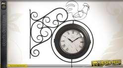 Horloge sur potence en fer forgé à double cadran