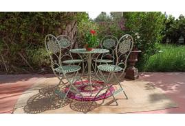 Salon de jardin en fer forgé coloris vert clair antique comprenant une table ronde et quatre chaises assorties