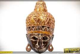 Sculpture sur bois de style oriental représentant une tête de bouddha, avec effet de dorure vieilli, présentée en forme de décoration murale en relief