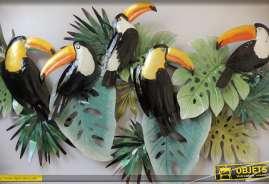 Fresque murale en métal peint : feuillages exotiques et perroquets perchés.