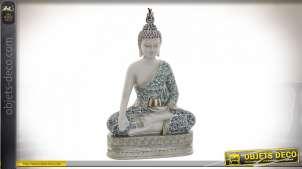 Représentation d'un bouddha en méditation sur socle, en résine finition blanc et notes brillantes, 29cm