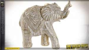 Statuette d'un éléphant en résine effet bois sculpté, reflets dorés sur fond brossé, 17cm