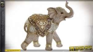 Représentation d'un éléphant avec habit oriental, finition dorée et facettes miroitées, en résine effet bois sculpté, 24cm