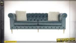 Grand canapé trois places capitonné style rétro finition velours bleu, série de deux coussins carrés fausse fourrure blanche, 230cm
