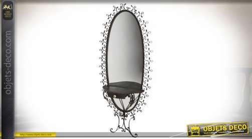 Grand miroir mural sur pied, en métal ouvragé façon fer forgé, patine noir, avec étagère et tiroir