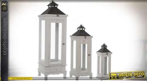 Ensemble décoratif composé de trois grandes lanternes de tailles décroisantes : 110 cm, 77 cm et 43 cm. En bois laqué blanc et métal noir veilli.