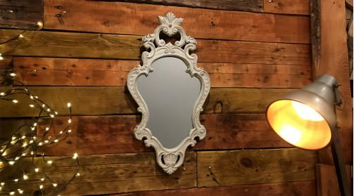 Miroir en bois sculpté d'inspirations baroques, finition blanchi ancien