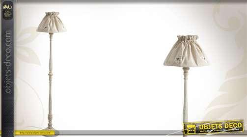 Lampadaire avec pied en bois tourné et abat-jour en coton coloris crème.