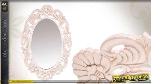 Miroir de forme ovale avec encadrement en bois sculpté, patine blanche.