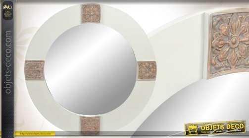 Miroir mural de forme ronde, réalisé en bois, coloris blanc et sculptures florales patinées.