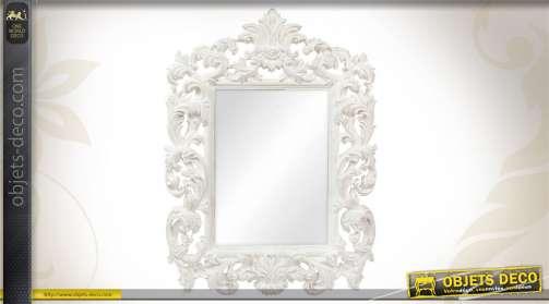 Miroir mural rectangulaire avec encadrement en résine, motifs floraux et végétaux, patine blanche.