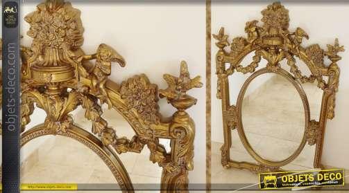 Miroir mural de style ancien, à parcloses, patiné coloris vieux doré, orné d'une décoration florale.