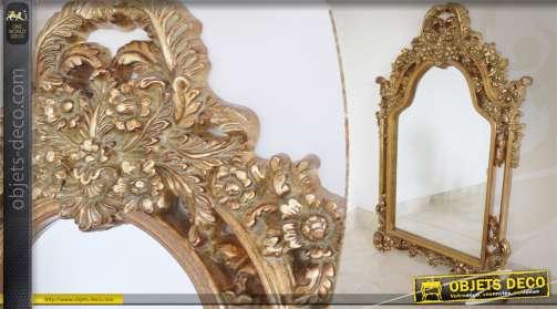 Grand miroir mural décoratif, avec encadrement ornemental, patiné en doré finition vieillie.