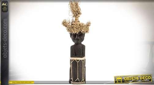 Sculpture sur bois, noir jais, d'un personnage avec ornementations en fibres végétales, style art Africain.