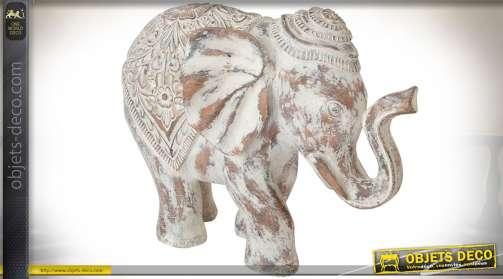 Grande statuette représentant un éléphant, en résine, rendu bois sculpté, aspect vieilli et blanchi, style oriental.