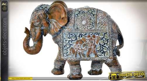 Statuette décorative en forme d'éléphant avec harnachement de parade, en résine, imitation bois sculpté vieilli et blanchi.