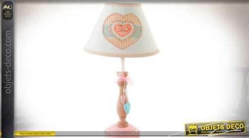 Lampe de chevet avec pied en bois tourné, teinte rose et bois naturel, et abat-jour en tissu blanc à motif de grand coeur. Utilise une ampoule de type