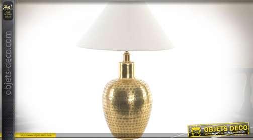 Lampe avec pied en forme de vase en métal doré brillant, motifs effet gaufré gravé esprit oriental. Abat-jour conique en tissu coloris blanc. Eclairag