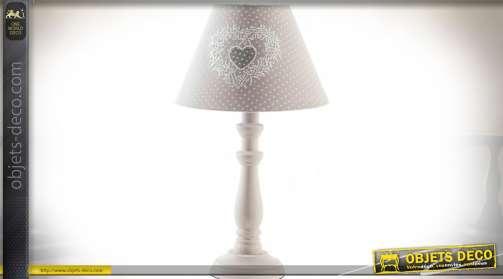 Ensemble de deux lampes à poser avec pieds en bois tourné patinés crème et abat-jour coniques en tissu gris clair à pois blancs et motifs en coeurs.