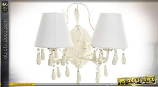 Applique de style charme et romantique en métal avec pampilles et deux abat-jour en tissu blanc de forme conique. Utilise deux ampoules de type E14.