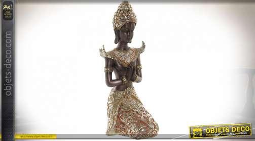 Statuette en résine d'une jeune femme balinaise en recueillement, finition doré ancien, 26cm